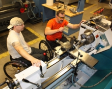 two men in wheelchair working on lab machines