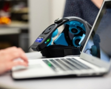 a picture of a hand on laptop ext to a headset
