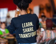"""the back of a standing individual wearing a shirt with the words """"LEARN. SHARE. TRANSFORM."""""""