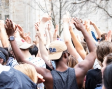 back of a crowd of students with one student wearing a Pitt hat