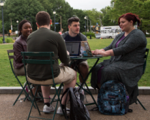 Four students sitting at a table outside talking
