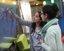 Two female students writing on an interactive teaching board
