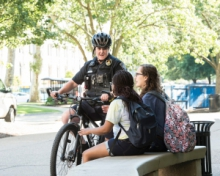a police officer on a bicycle talking to two students sitting by a bench