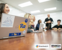 students sitting around table with laptop. Brandwatch and Brand24 logos on bottom right corner