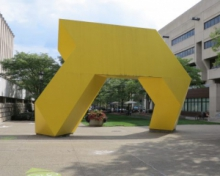 Yellow art sculpture next to the Barco Law Building on campus